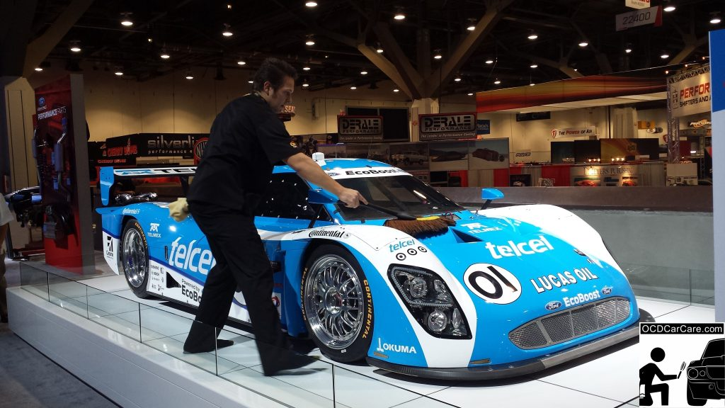 OCDCarCare at SEMA 2013 - Christopher Brown of OCDCarCare dusting down a Ford race car.