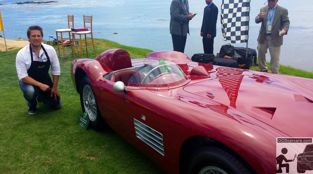Christopher Brown, of OCDCarCare Los Angeles, kneels beside the 1956 Maserati 150S after judging for the 2014 Pebble Beach Concours d' Elegance.